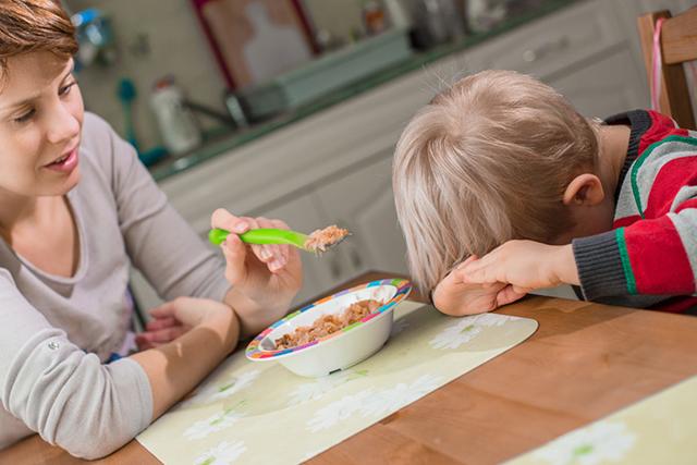 Мать кормит сына